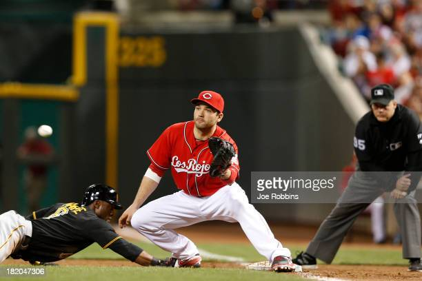 Joey Votto of the Cincinnati Reds takes the throw at first base ahead of the slide by Starling Marte of the Pittsburgh Pirates during the game at...