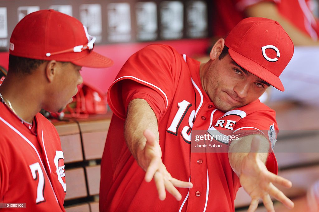 Joey Votto of the Cincinnati Reds talks with Ramon Santiago of the Cincinnati Reds about hitting in the dugout during the seventh inning against the...