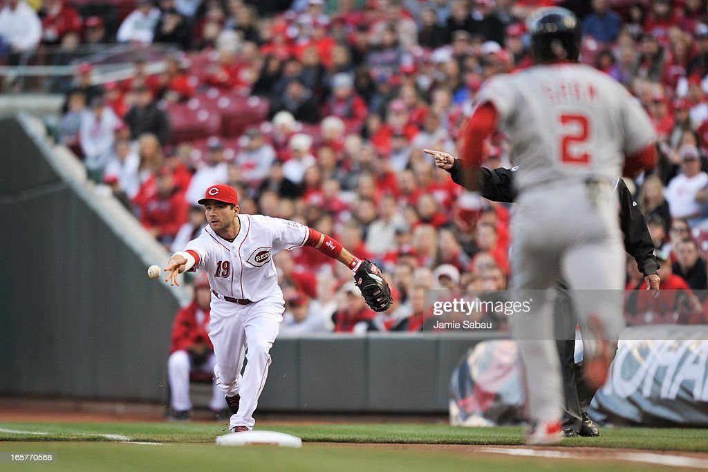 <a gi-track='captionPersonalityLinkClicked' href=/galleries/search?phrase=Joey+Votto&family=editorial&specificpeople=759319 ng-click='$event.stopPropagation()'>Joey Votto</a> #19 of the Cincinnati Reds tosses the ball to pitcher <a gi-track='captionPersonalityLinkClicked' href=/galleries/search?phrase=Homer+Bailey&family=editorial&specificpeople=759409 ng-click='$event.stopPropagation()'>Homer Bailey</a> #34 of the Cincinnati Reds for the out on <a gi-track='captionPersonalityLinkClicked' href=/galleries/search?phrase=Denard+Span&family=editorial&specificpeople=835844 ng-click='$event.stopPropagation()'>Denard Span</a> #2 of the Washington Nationals in the first inning at Great American Ball Park on April 5, 2013 in Cincinnati, Ohio.