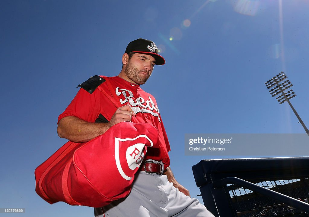 Joey Votto of the Cincinnati Reds walks into the dugout before the spring training game against the San Diego Padres at Peoria Stadium on February 26...