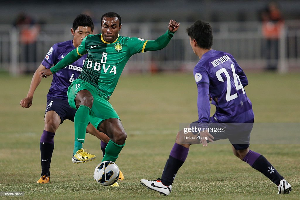 Joffre David Guerron Mendez (C) of Beijing Guo'an controls the ball with Hiroki Mizumoto (L) and Gakuto Notsuda of Hiroshima Sanfrecce celebrates scoring his first goal during the AFC Champions League Group match between Hiroshima Sanfrecce and Beijing Guoan at Beijing Workers' Stadium on March 13, 2013 in Beijing, China.