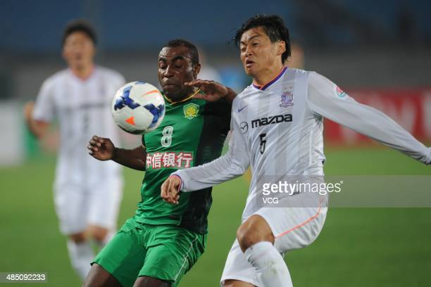 Joffre Guerron of Beijing Guo'an and Kazuhiko Chiba of Sanfrecce Hiroshima battle for the ball during the Asian Champions League match between...