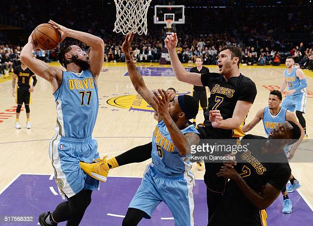 Joffrey Lauvergne of the Denver Nuggets pulls down a rebound against Larry Nance Jr #7 of the Los Angeles Lakers as Will Barton of the Denver Nuggets...