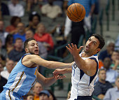 Joffrey Lauvergne of the Denver Nuggets scrambles for the ball against Zaza Pachulia of the Dallas Mavericks in the first half at American Airlines...