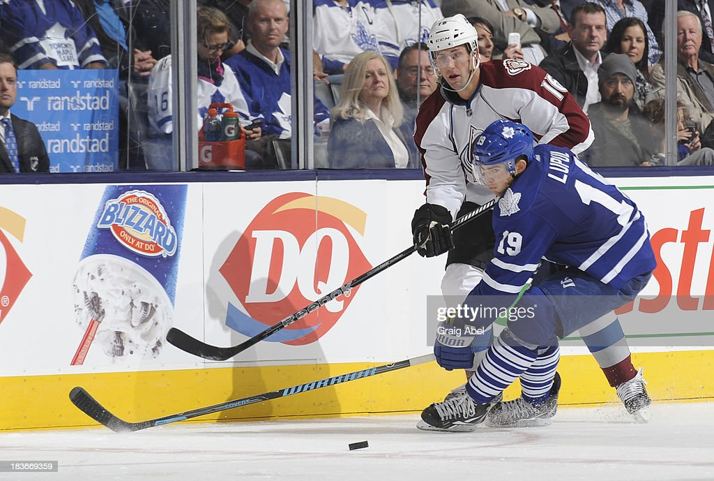 Joffrey Lupul #19 of the Toronto Maple Leafs battles for the puck with Cory Sarich #16 of the Colorado Avalanche during NHL game action October 8, 2013 at Air Canada Centre in Toronto, Ontario, Canada.