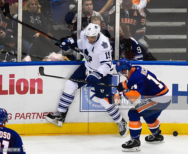 Joffrey Lupul of the Toronto Maple Leafs fights for the puck with Thomas Hickey of the New York Islanders in the second period at Nassau Veterans...