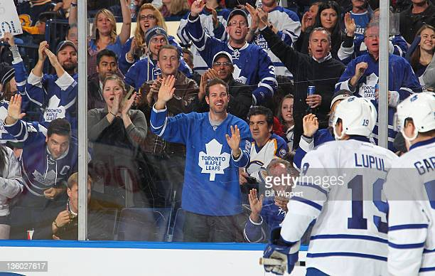 Joffrey Lupul of the Toronto Maple Leafs heads to the bench to celebrate his second period goal against the Buffalo Sabres while being cheered on by...