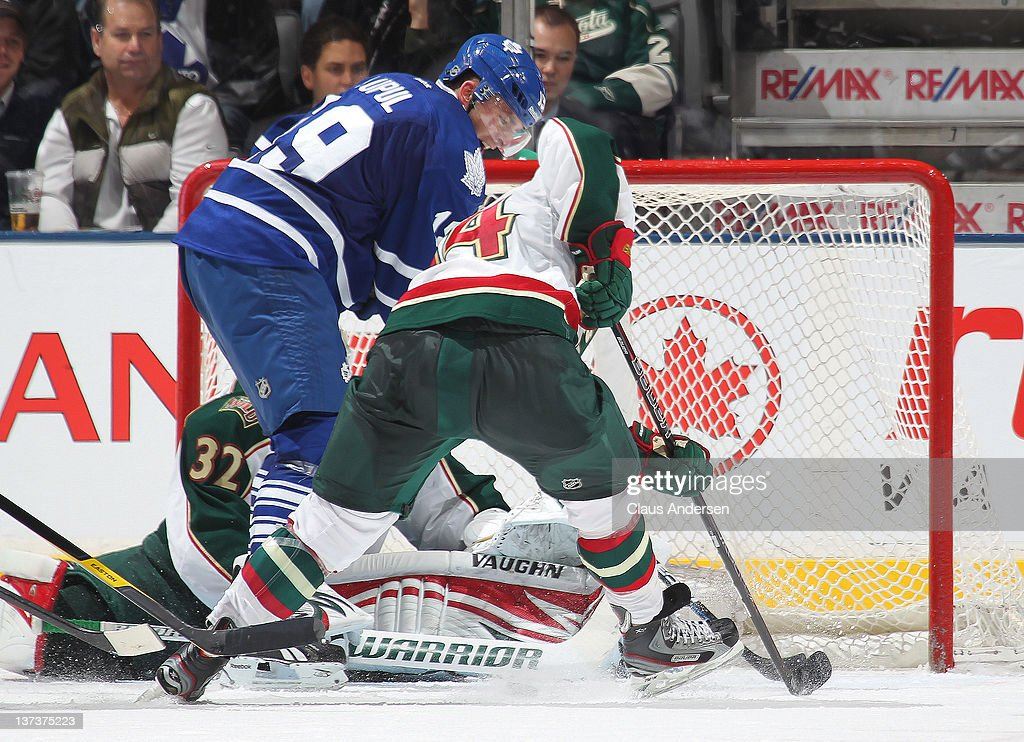 Joffrey Lupul #19 of the Toronto Maple Leafs is stopped on a scoring attempt by Darroll Powe #14 of the Minnesota Wild in a game on January 19, 2012 at the Air Canada Centre in Toronto, Ontario, Canada. The Leafs defeated the Wild 4-1.