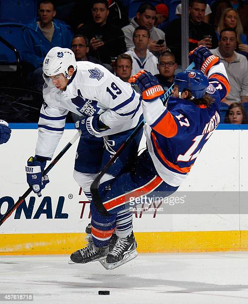 Joffrey Lupul of the Toronto Maple Leafs issues a hard check to Matt Martin of the New York Islanders during the first period at the Nassau Veterans...