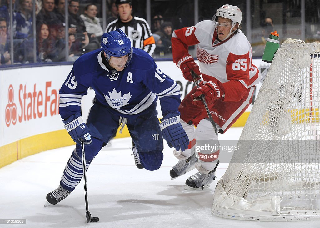 Joffrey Lupul #19 of the Toronto Maple Leafs skates the puck away from Danny DeKeyser #65 of the Detroit Red Wings during NHL game action March 29, 2014 at the Air Canada Centre in Toronto, Ontario, Canada.