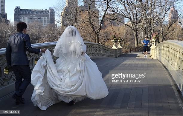 A jogger approaches newlyweds getting ready to pose for wedding photos on the Bow Bridge in Central Park as New Yorkers and tourists take advantage...