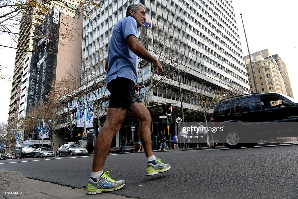 A jogger crosses the road in front of the Reserve Bank of Australia (RBA) headquarters in the central business district of Sydney, Australia, on Monday, July 15, 2013. While the RBA previously needed higher interest rates to control price pressures as the Australian economy expanded since 1991 without a recession, Governor Glenn Stevens has slashed the cash target, predicting a mining boom will wane. Photographer: Dan Himbrechts/Bloomberg via Getty Images