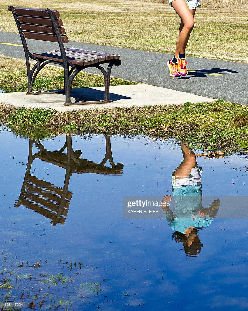 A jogger is reflected in water as she runs on a warm sunny day in Alexandria, Virginia on March 9, 2013. The weather Saturday was in stark contrast to that of only a couple of days ago, when a winter storm hammered the East coast. AFP PHOTO / Karen BLEIER