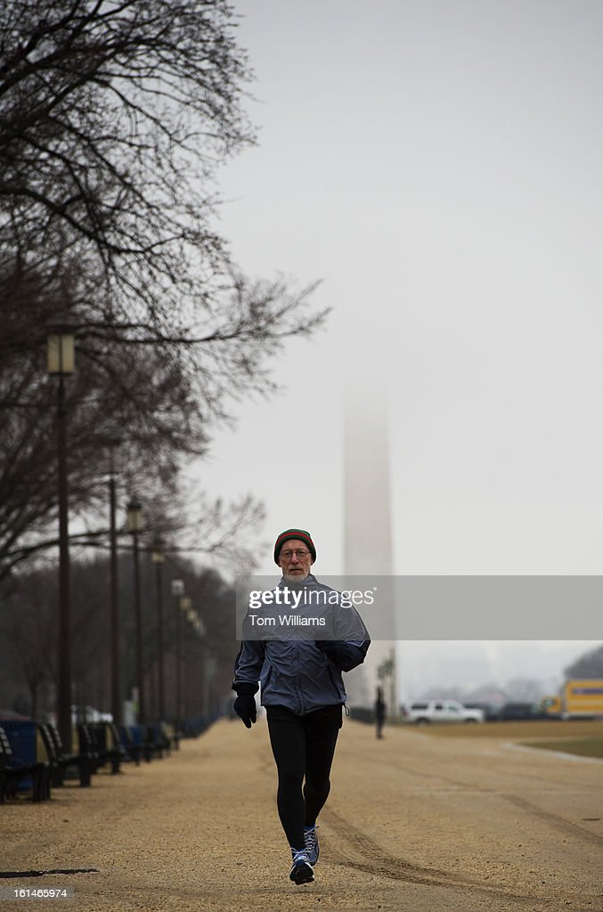 A jogger makes his way down the National Mall as fog obscures the Washington Monument.