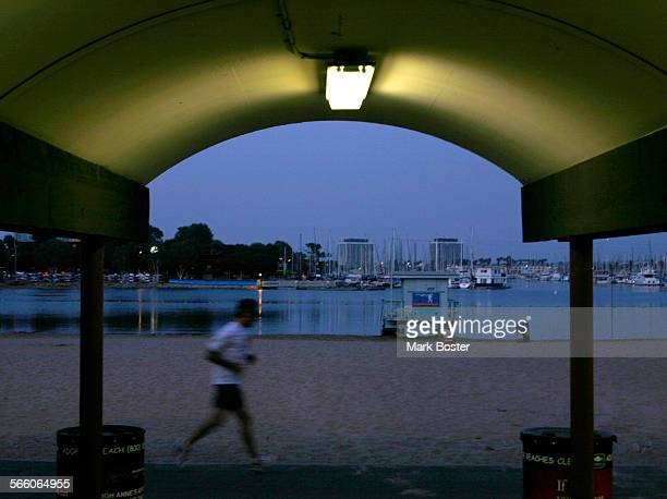 A jogger makes the most of a cool evening at Mothers Beach in Marina del Rey July 16 2008 as he passes one of the picnic bungaloes The tranquility of...