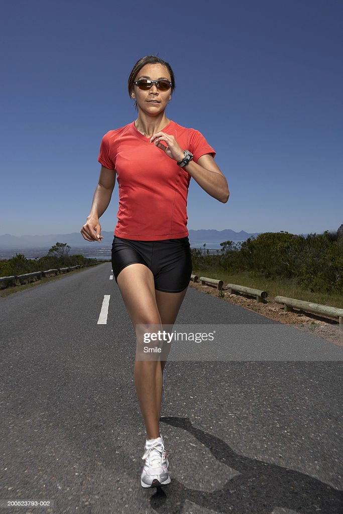 Jogger on country road, front view : Stock Photo
