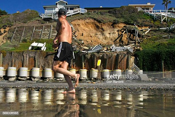 DECEMBER 28 2010 ENCINITAS CA A jogger on Leucadia State Beach in Encinitas CA looks up a bluff that collapsed below a house at 1500 Neptune Dr The...