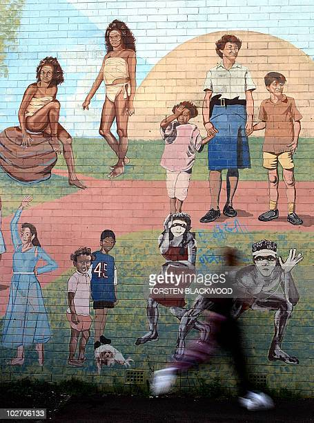 A jogger passes a mural featuring Aboriginal children by Australian artist Michael Byrt in the indigenous community of Redfern in Sydney 15 October...