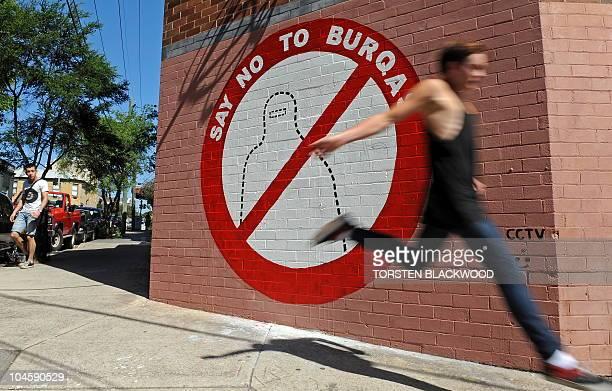 A jogger passes Australian artist Sergio Redegalli's antiburqa mural on the wall of his studio in Sydney on September 30 2010 Sergio's studio has...