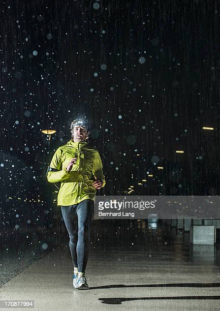 Jogger running in the rain, at night