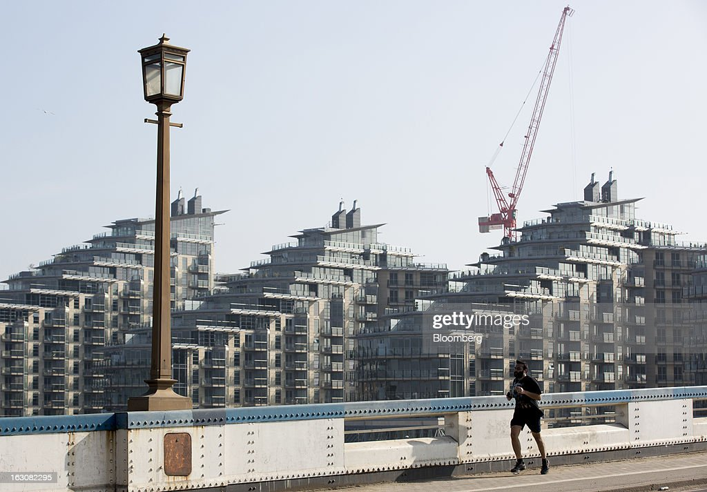 A jogger runs across Wandsworth bridge past the Battersea Reach Housing Development in London, U.K., on Monday, March 4, 2013. Central London luxury-home prices unexpectedly rose at the fastest pace in 10 months in February as the British pound's depreciation helped attract international investors, Knight Frank LLP said. Photographer: Jason Alden/Bloomberg via Getty Images