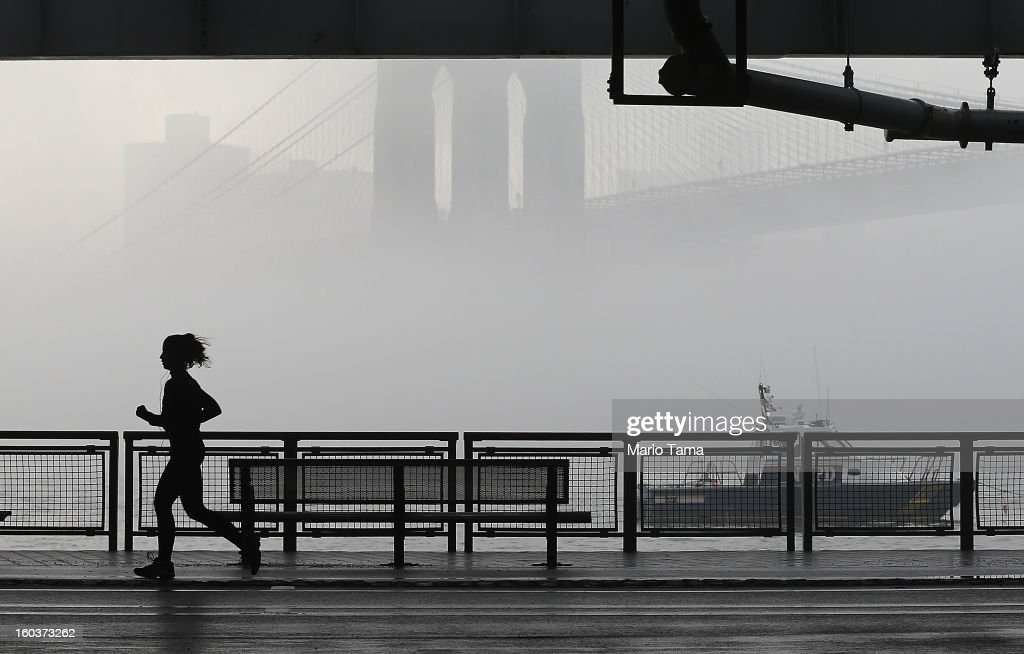 A jogger runs along the East River past morning fog and an NYPD patrol boat on January 30, 2013 in New York City. Temperatures are expected to reach into the upper 50's today in the city.