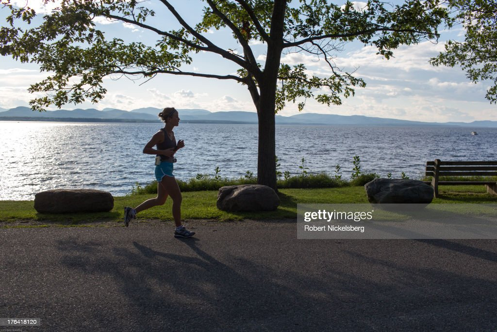 A jogger runs along the shore of Lake Champlain August 3, 2013 in Charlotte, Vermont. The Adirondack Mountains and New York state lie across the lake.