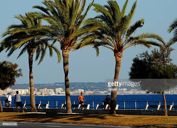 A jogger runs backdropped by the Mediterranean Sea and playa Ciudad Jardin on August 14 2009 in Palma de Mallorca Spain