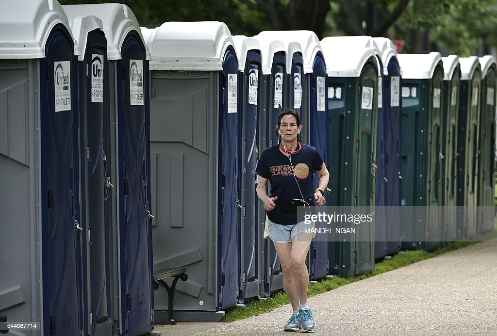 A jogger runs byrows of portable toilets on July 1, 2016, near the Washington Monument on the Mall, a popular spot to watch the Independence Day holiday fireworks, in Washington, DC. / AFP / Mandel Ngan