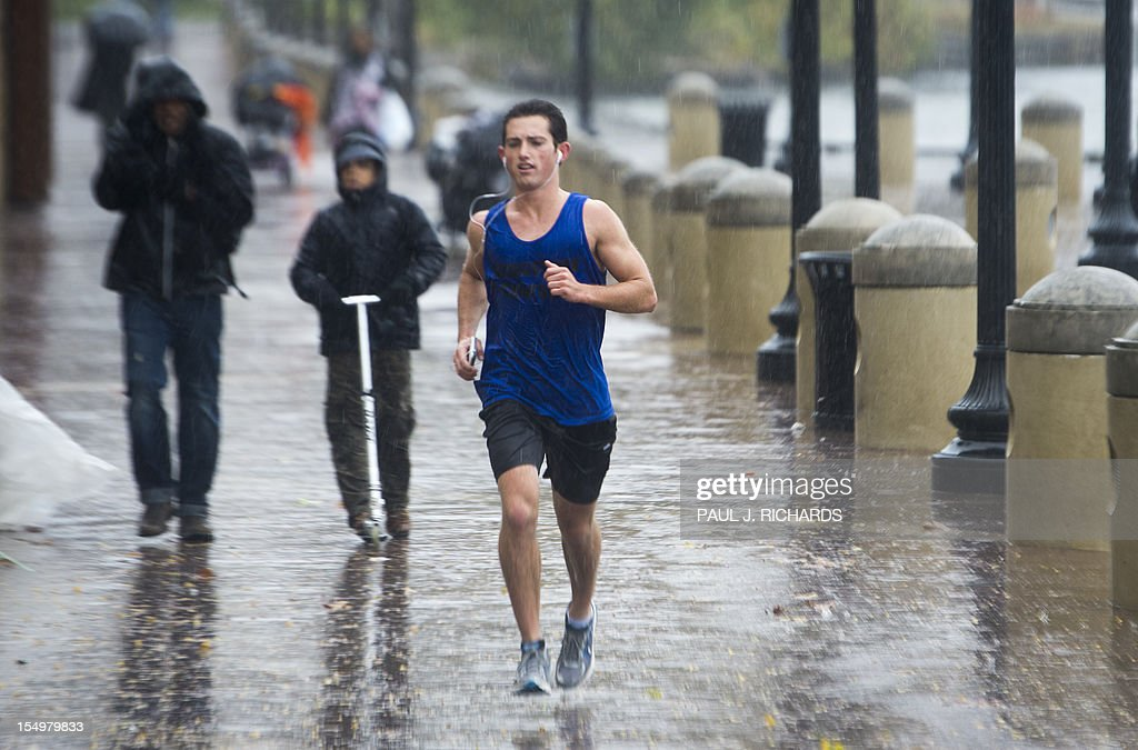 A jogger runs in the rain as Hurricane Sandy rains on the Washington Harbor area located on the Potomac River on October 29, 2012 in the Georgetown area of Washington. AFP PHOTO/Paul J. Richards