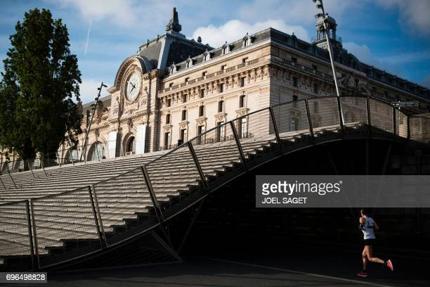 TOPSHOT A jogger runs near of the Orsay museum in Paris on June 16 2017 / AFP PHOTO / JOEL SAGET