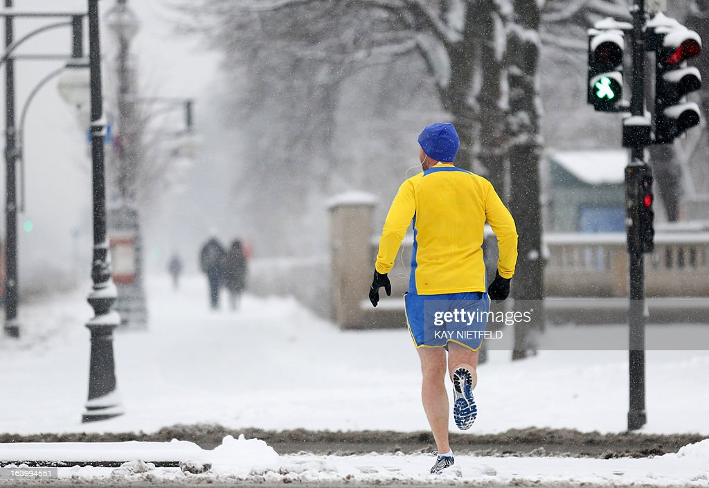 A jogger runs on a snow-covered street during a snowfall in Berlin, on March 19, 2013. OUT +++