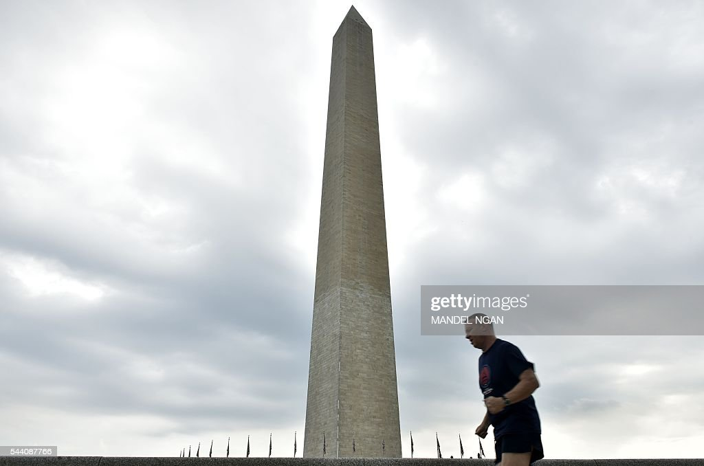 A jogger runs on July 1, 2016, near the Washington Monument on the Mall, a popular spot to watch the Independence Day holiday fireworks, in Washington, DC. / AFP / Mandel Ngan