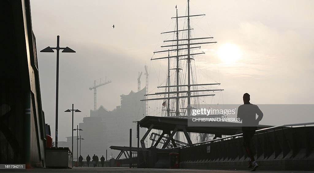A jogger runs over a landing bridge at the port of Hamburg northern Germany as in background can be seen the 'Elbphilharmonie' opera house under...