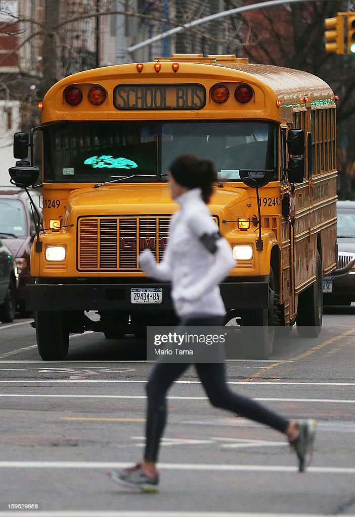 A jogger runs past a school bus in Manhattan's East Village on January 15, 2013 in New York City. Drivers of the city's school buses are set to go on strike tomorrow after negotiations with Mayor Michael Bloomberg failed to reach an agreement; over 150,000 children will need to find an alternate method of transportation to school.