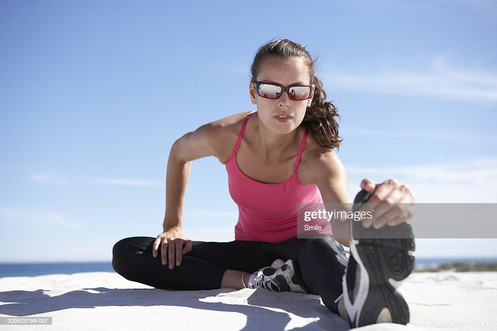 Jogger stretching on beach : Stock Photo