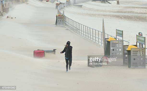 A jogger struggles against sand whipped up by strong winds at Bondi Beach in Sydney on April 21 2015 Sydney and surrounding areas were lashed by wild...
