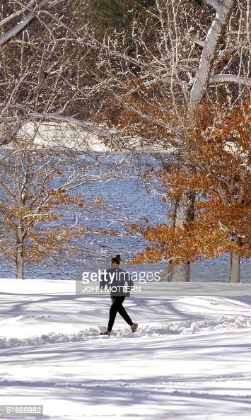 A jogger takes advantage of the calm after the storm in Wellesley Massachusetts 26 December 2002 after a heavy snow fall hit the North East of the...