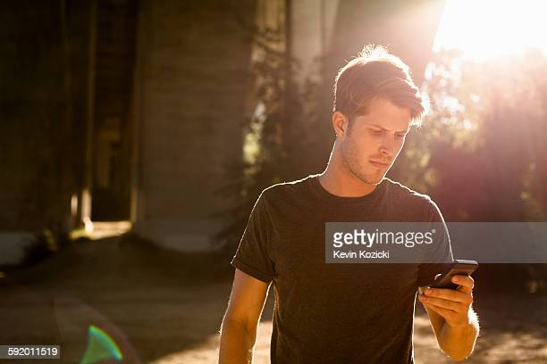 Jogger using phone under arch bridge, Arroyo Seco Park, Pasadena, California, USA