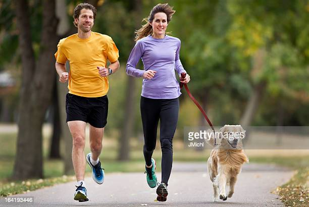 Joggers and Golden Retriever Running on a Paved Trail.