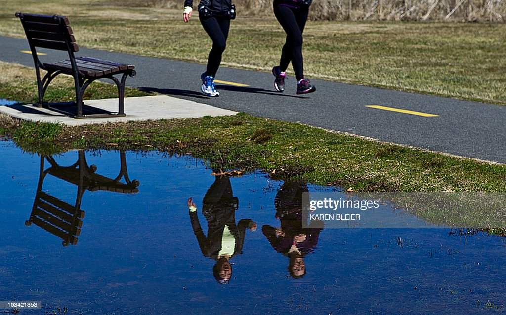 Joggers are reflected in water as they run along the Mt. Vernon trail on a warm sunny day in Alexandria, Virginia, on March 9, 2013. The weather was in stark contrast to that of only a couple of days ago, when a winter storm hammered the East coast. AFP PHOTO / Karen BLEIER