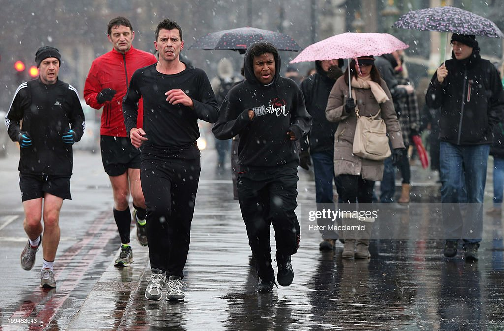 Joggers brave snow flurries as they cross Westminster Bridge on January 14, 2013 in London, England. Heavy snow is falling in parts of the United Kingdom.