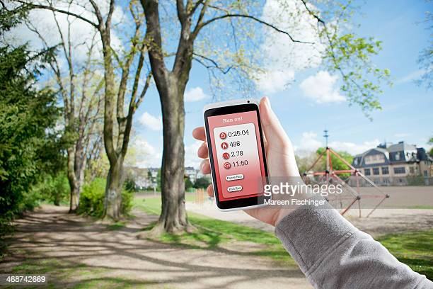 Jogger?s hand holding phone with running app
