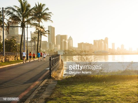 Joggers on a promenade at sunrise