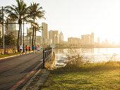 Joggers on a promenade at sunrise