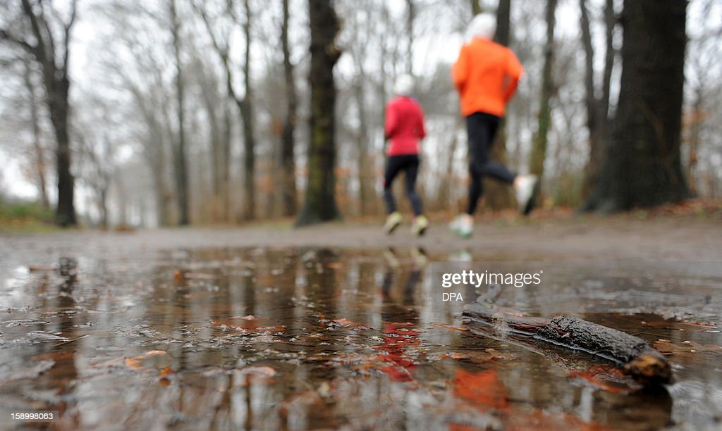 Joggers run past puddles in a park in Hamburg, northern Germany, on January 5, 2013.