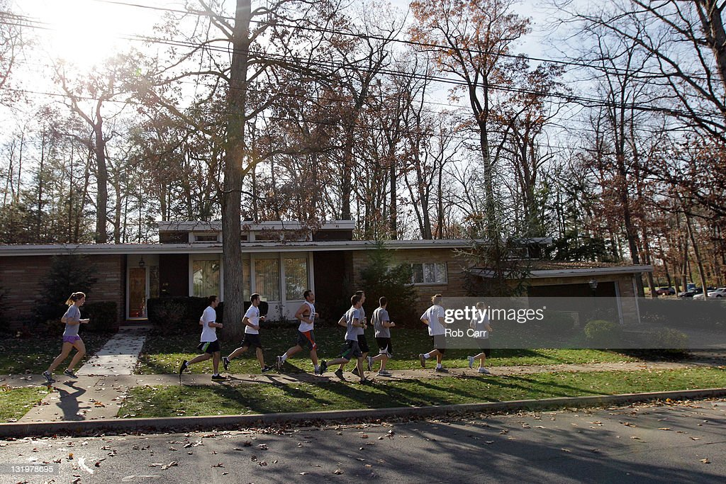 Joggers run past the home of Penn State University head football coach Joe Paterno on November 9, 2011 in State College, Pennsylvania.