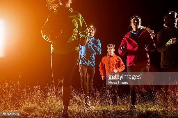Joggers running on field at night