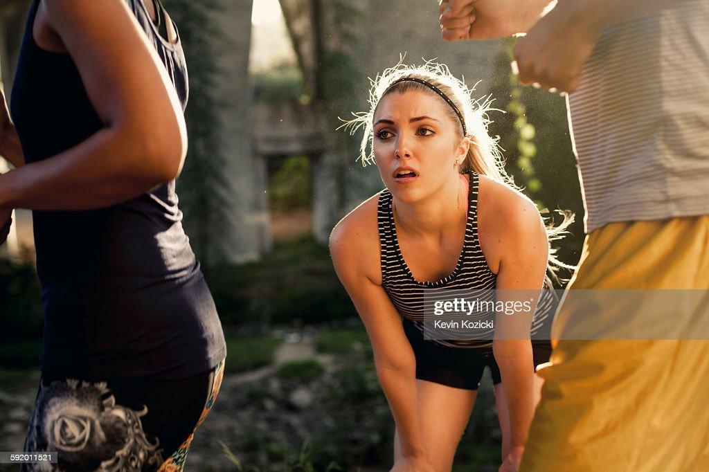 Joggers running past jogger taking break, Arroyo Seco Park, Pasadena, California, USA