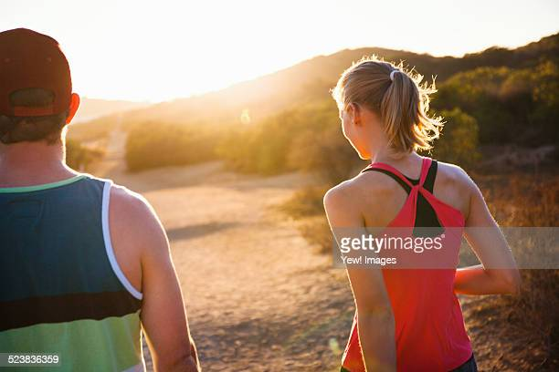 Joggers walking on sunlit path, Poway, CA, USA